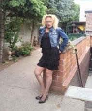 Eine Blondine posiert draussen im kurzen Rock