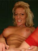 Eine Blondine trägt rote Strapsstrümpfe und spreizt ihre Beine